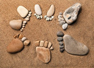 trace feet of a pebble stone on the sea sand backdrop , concept